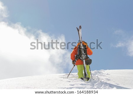 Skier climbing a snowy mountain - stock photo
