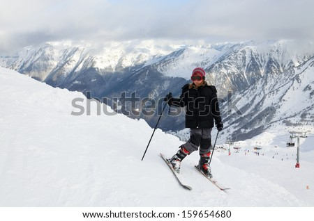 Skier-girl is standing on the snow-covered hill at the Cirque du Lys. There is range of mountains (Soum de Mauloc) in the background. Winter Pyrenees is photographed at the Cauterets ski resort. - stock photo