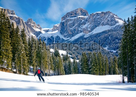 Skier going down the slope at Val Di Fassa ski area in Italy - stock photo