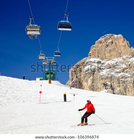 Skier going down the slope under ski lift at Sella Ronda ski route in Italy - stock photo