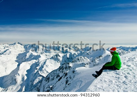 Skier having a break, sitting on the edge and being overwhelmed by beauty of high mountains, Austrian Alps below - stock photo