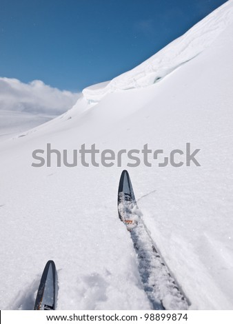 Skier hesitating before passing a dangerous snow formation - stock photo