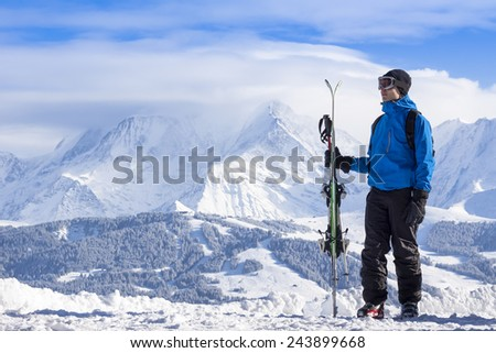 Skier holding skis and looking at beautiful snow covered valley