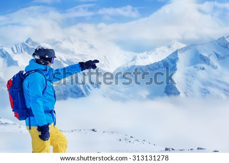 Skier in helmet and goggles with backpack pointing at high snowy mountains - stock photo