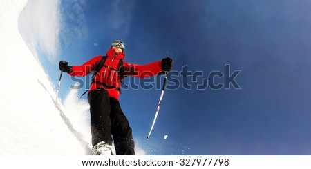 Skier in mountains performs a high speed turn on a ski piste. Sunny winter day. Concepts: vacation, speed, fun. Large copy-space on the right for title or text.
