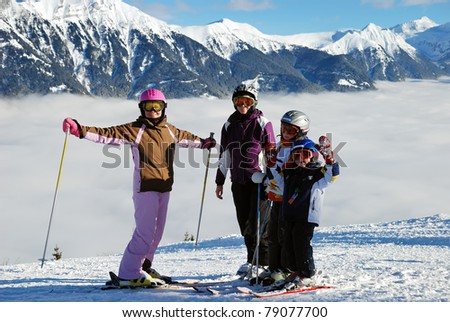 skier in the beautiful alps. Kids and adults  in the high snowy cloudy mountains in winter. - stock photo