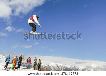 Skier instructor doing high jump above the mountain and group people at Switzerland alps. Swiss. Freestyle. Winter sport. Healthy lifestyle. Pro.
