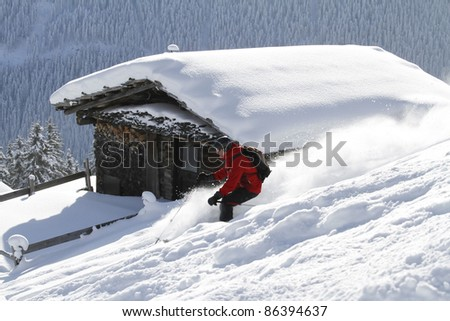 Skier is skiing back country with blockhouse in the background - stock photo