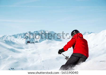 Skier is skiing downhill. Skiing resort  in the background