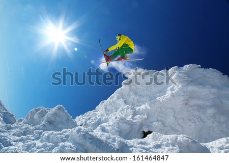 Skier jumping against blue sky from the rock