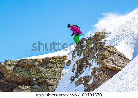 Skier jumping off a cliff in the mountains on a sunny day - stock photo