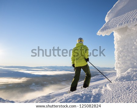 Skier looking out over partly cloud covered valley. - stock photo
