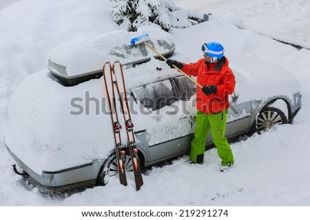 Skier man is shoveling the car of snow - stock photo