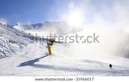 skier near a snow cannon which is making powder snow