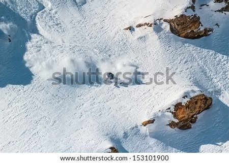 Skier on a steep slope among the rocks. In turn raises the snow dust.