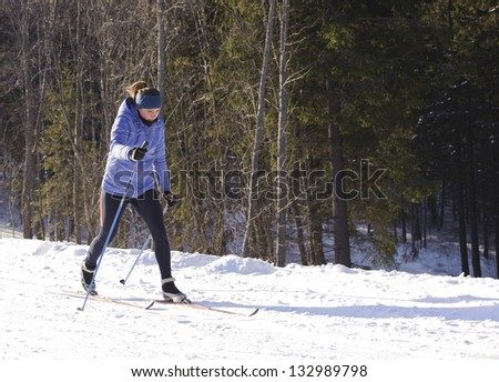 Skier on a walk in the park in winter - stock photo