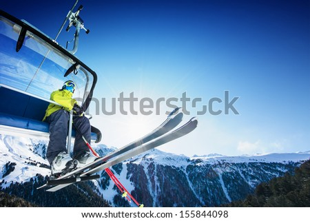 Skier on lift in mountains - stock photo