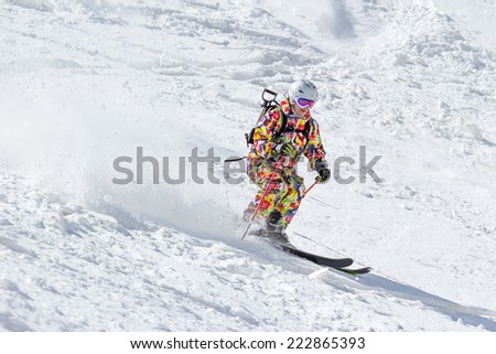 Skier on mountain slope off piste in soft snow on a sunny day