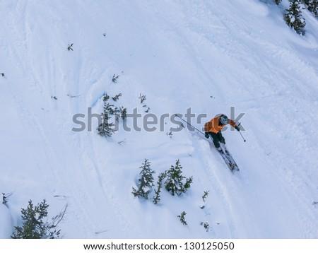 Skier on steep slope - stock photo