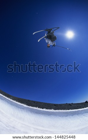Skier performing flip on mountain against clear blue sky with fisheye shot - stock photo