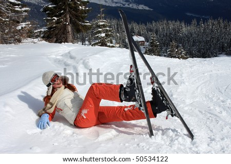Skier, put on shoes in pattens, lies to snow - stock photo