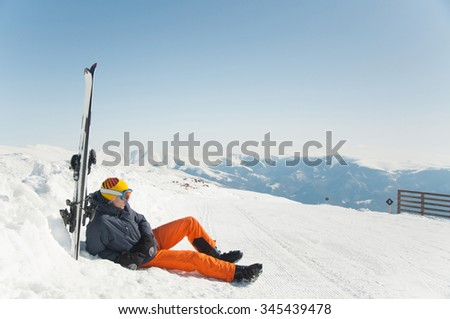 Skier relaxing at mountain ski resort with beautiful landscape