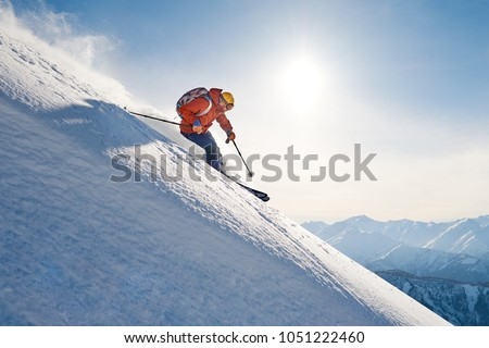 skier rides freeride on powder snow down the slope against the backdrop of the mountains