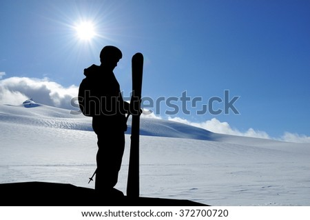 Skier silhouette high in mountains. Skier ready for freeride standing on a hill and holding ski, snowy hills and sun behind him. - stock photo