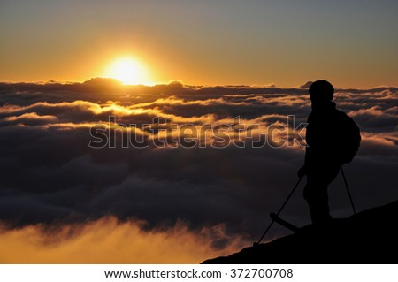 Skier silhouette high in mountains. Skier standing on a hill high above the clouds during a sunset, beautiful colorful sky with clouds in front of him. - stock photo