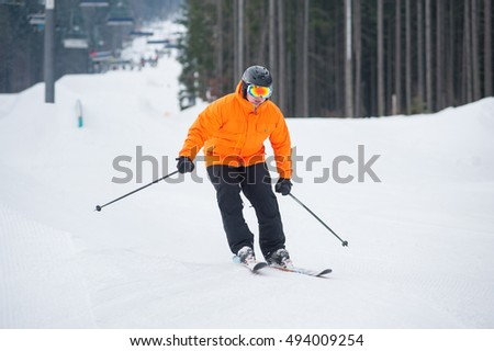 Skier skiing downhill at ski resort against ski-lift and forest. Male is wearing orange jacket, helmet and goggles. Carpathian Mountains, Bukovel