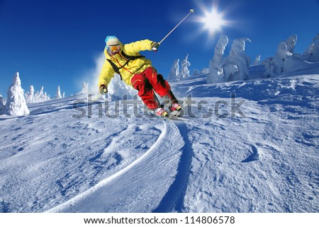 Skier skiing downhill in high mountains - stock photo