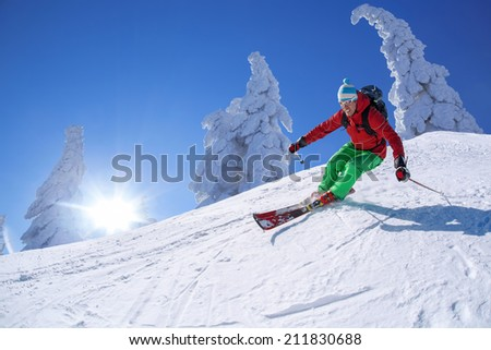 Skier skiing downhill in high mountains against sunset - stock photo