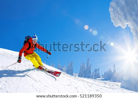 Skier skiing downhill in high mountains against sunshine