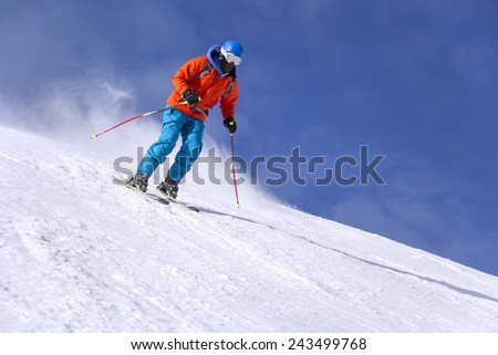 Skier skiing downhill in high mountains and sunny day - stock photo