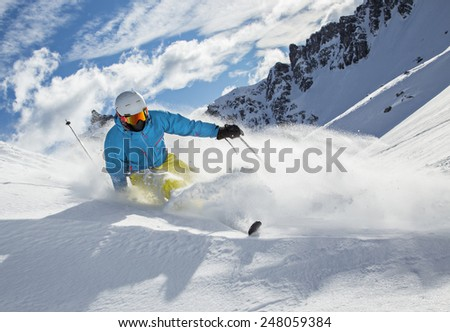 Skier skiing downhill in high mountains during sunny day. - stock photo