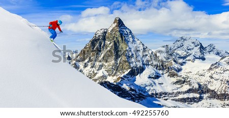 Skier skiing downhill in high mountains in fresh powder snow. Snow mountain range with Matterhorn in background. Zermatt Alps region Switzerland.