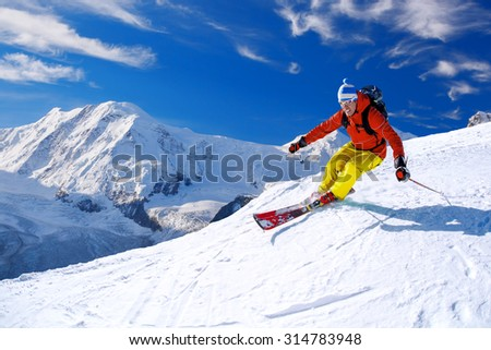Skier skiing downhill in high mountains, Matterhorn area, Switzerland - stock photo