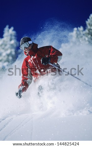 Skier skiing in powder snow against clear sky - stock photo
