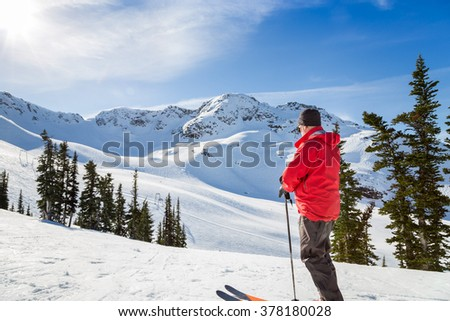 Skier standing in front of Whistler Mountain peak.  - stock photo