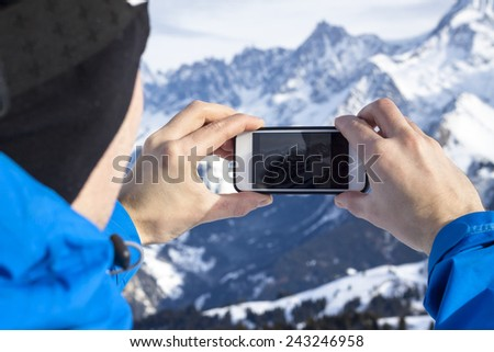 Skier taking photos with smartphone in hands - stock photo