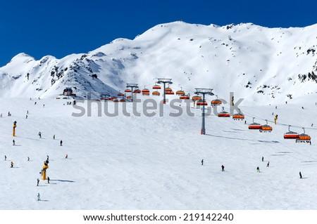 Skiers and orange chairlift in Alpine ski resort in Solden in Otztal Alps, Tirol, Austria - stock photo