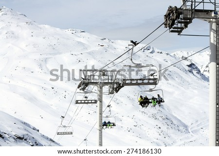 Skiers and snowboarder ride a chairlift up a mountain on a ski resort during winter on a bright day. - stock photo