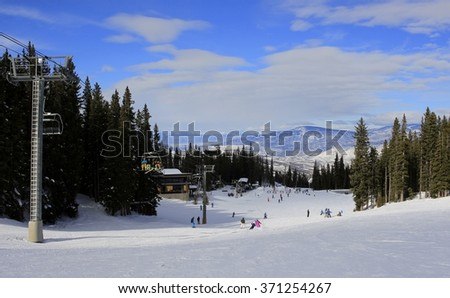 Skiers and snowboarders getting down to a chairlift; mountains in the background