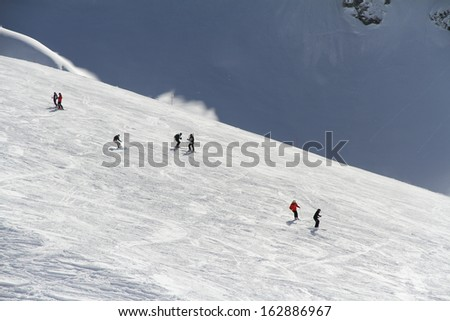 Skiers and snowboarders going down the slope at ski resort. Krasnaya Polyana, Sochi, Russia