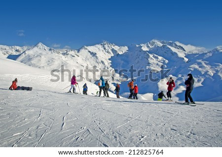 Skiers at the beginning of a ski slope, snowy peaks of the Alps, France - stock photo