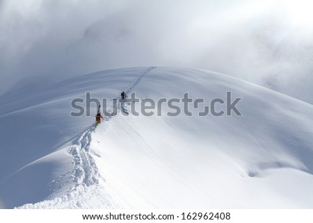 Skiers climbing a snowy mountain - stock photo