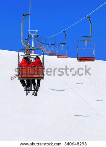 Skiers couple in red skisuits go on a ski lift against winter snowy mountain landscape and blue sky - stock photo