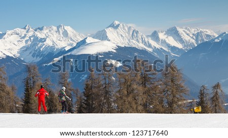 Skiers cruising down a ski run in the Alps. - stock photo