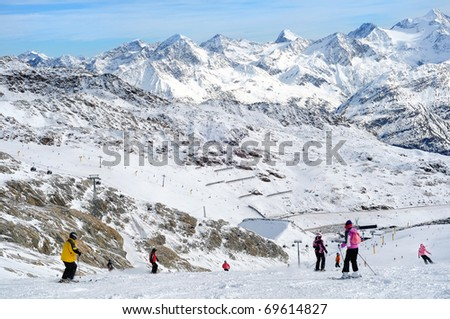 Skiers having fun on wide slopes of Austrian glacier in Solden. Wonderful view.