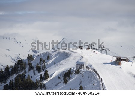 Skiers in the high alps with distant clouds - stock photo